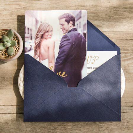 Invitación de boda con foto sobre azul y detalles en dorado.